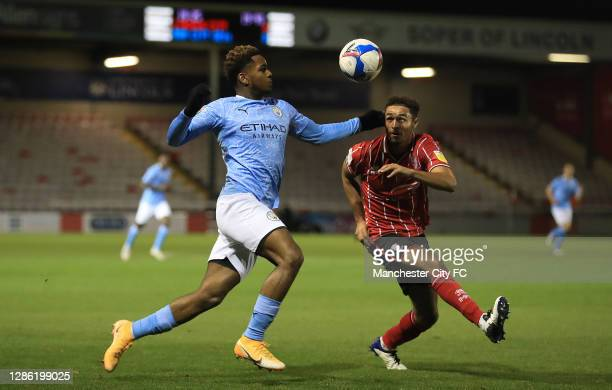 Jaden Braaf of Manchester City U21 and Max Melbourne of Lincoln City challenge for the ball during the EFL Trophy match between Lincoln City and...