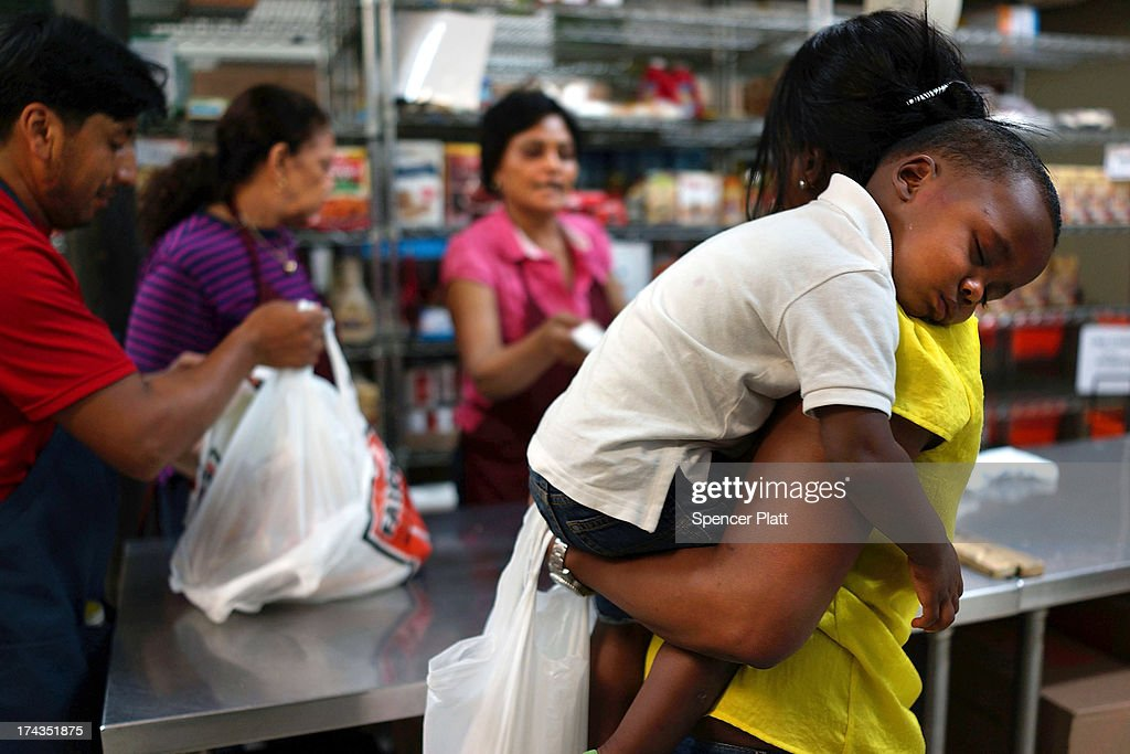 Jaden Painegua (2) rests on his mother's shoulder at the West Side Campaign Against Hunger food bank on July 24, 2013 in New York City. The food bank assists thousands of qualifying New York residents in providing a monthly allotment of food. In an anticipated speech today in Illinois, President Obama tried to re-focus the nations attention back onto the economy and the growing inequality between the rich and the rest of America. As of May 2013 the unemployment rate in America was stuck at 7.6% with many more Americans having given up on looking for work.