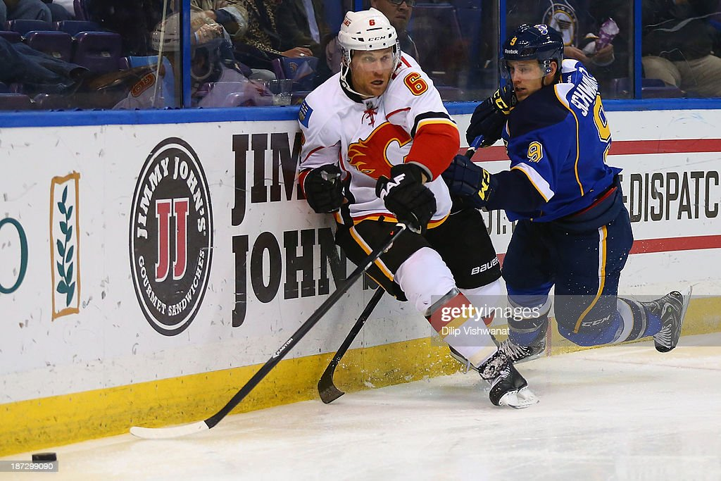 Jaden Schwartz #9 of the St. Louis Blues and Dennis Wideman #6 of the Calgary Flames chase down a loose puck at the Scottrade Center on November 7, 2013 in St. Louis, Missouri. The Blues beat the Flames 3-2.