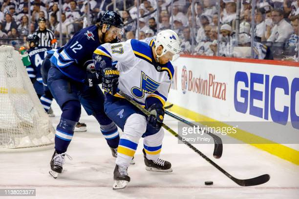 Jaden Schwartz of the St Louis Blues plays the puck behind the net as Kevin Hayes of the Winnipeg Jets defends during third period action in Game...