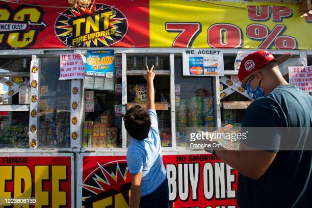 Jaden Veal left and his father James Veal right both of Hawthorne purchase fireworks five days prior to the 4th of July at a fireworks stand on...