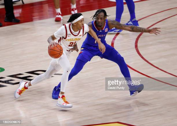 Jaden Walker of the Iowa State Cyclones drives the ball as Marcus Garrett of the Kansas Jayhawks puts pressure on in the second half of play at...