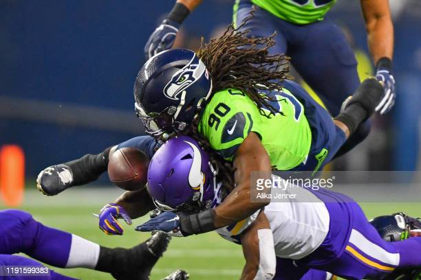 Jadeveon Clowney of the Seattle Seahawks, top, knocks the ball loose from Dalvin Cook of the Minnesota Vikings during the game at CenturyLink Field...