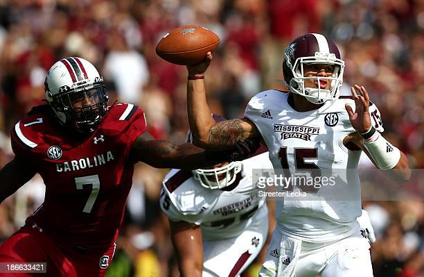 Jadeveon Clowney of the South Carolina Gamecocks tries to stop Dak Prescott of the Mississippi State Bulldogs as he drops back to pass during their...