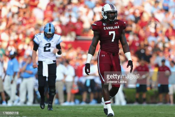 Jadeveon Clowney of the South Carolina Gamecocks watches on as Bryn Renner of the North Carolina Tar Heels follows behind during their game at...