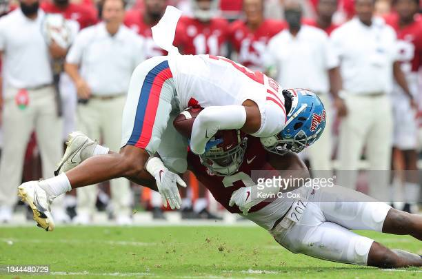 Jadon Jackson of the Mississippi Rebels pulls in this reception as he is tackled by DeMarcco Hellams of the Alabama Crimson Tide during the first...