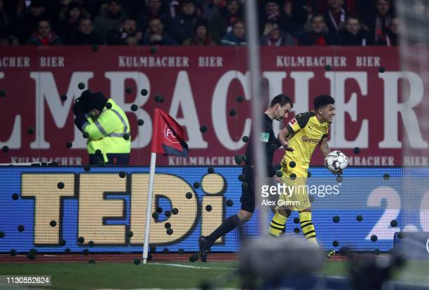 Jadon Malik Sancho of Borussia Dortmund tires to take a corner as he is pelted with black balls thrown at him by Nurnberg fans during the Bundesliga...