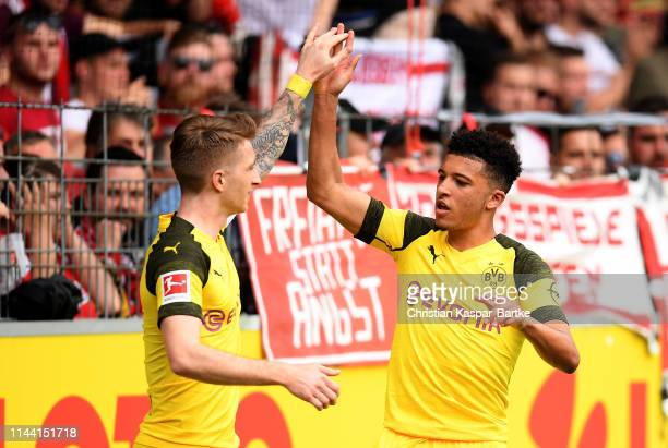 Jadon Malik Sancho of Dortmund celebrate with team mate Marco Reus after he scores the opening goal during the Bundesliga match between SportClub...