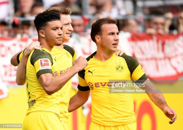 Jadon Malik Sancho of Dortmund celebrate with team mates Marco Reus and Mario Goetze after he scores the opening goal during the Bundesliga match...