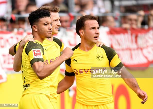 Jadon Malik Sancho of Dortmund celebrate with team mates Marco Reus and Mario Goetze after he scores the opening goal during the Bundesliga match...