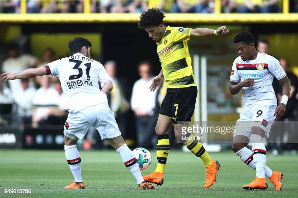 Jadon Malik Sancho of Dortmund fights for the ball with Kevin Volland of Bayer Leverkusen and Leon Bailey of Bayer Leverkusen during the Bundesliga...