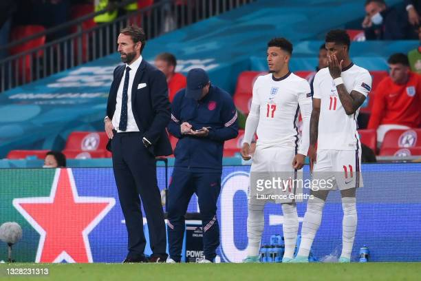 Jadon Sancho and Marcus Rashford of England wait to be substituted on next to Gareth Southgate, Head Coach of England during the UEFA Euro 2020...