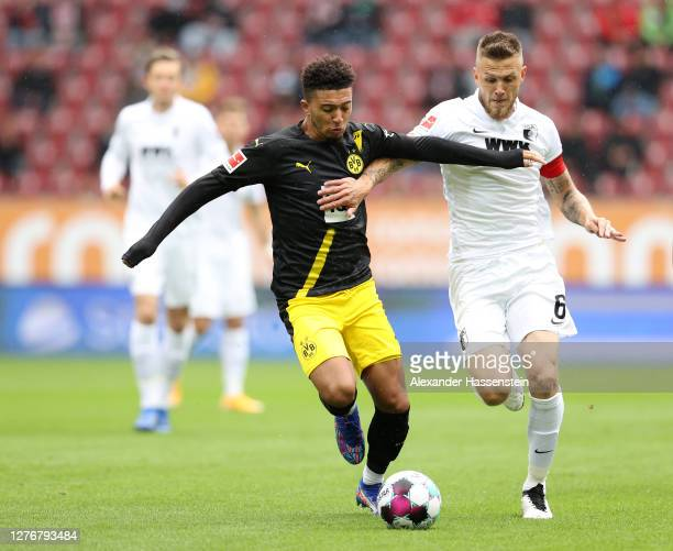 Jadon Sancho of Borussia Dortmund battles for possession with Jeffrey Gouweleeuw of FC Augsburg during the Bundesliga match between FC Augsburg and...
