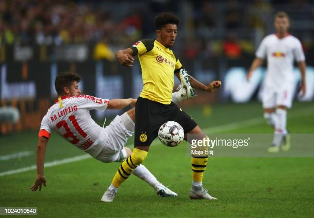 Jadon Sancho of Borussia Dortmund battles for possession with with Diego Demme of RB Leipzig during the Bundesliga match between Borussia Dortmund...