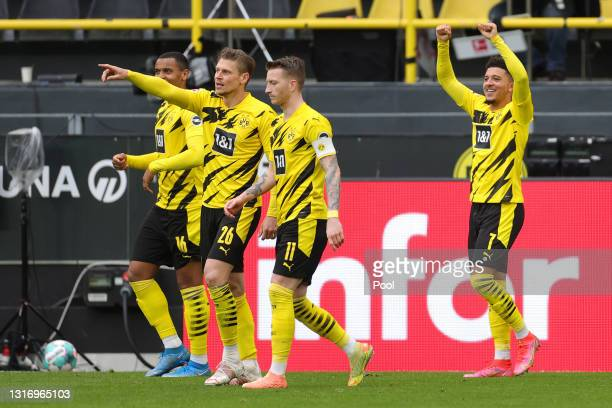 Jadon Sancho of Borussia Dortmund celebrates after scoring their team's second goal as Lukasz Piszczek and Marco Reus look on during the Bundesliga...