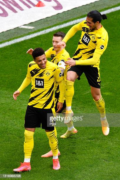Jadon Sancho of Borussia Dortmund celebrates with Marco Reus and Emre Can after scoring their team's second goal during the Bundesliga match between...