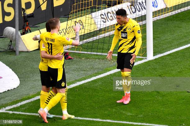 Jadon Sancho of Borussia Dortmund celebrates with teammate Marco Reus after scoring his team's third goal during the Bundesliga match between...