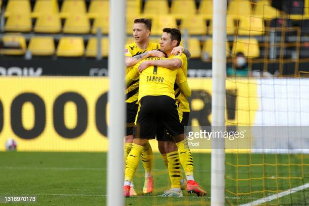 Jadon Sancho of Borussia Dortmund celebrates with teammates Marco Reus and Raphael Guerreiro after scoring his team's third goal during the...