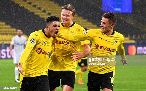 Jadon Sancho of Borussia Dortmund celebrates with teammates Thorgan Hazard and Erling Haaland after scoring his team's first goal from the penalty...