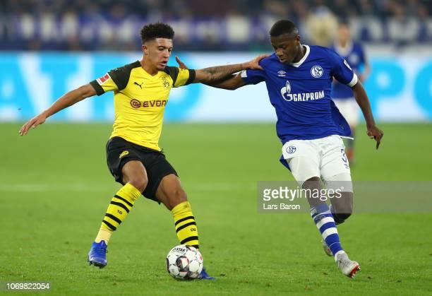 Jadon Sancho of Borussia Dortmund is challenged by Hamza Mendyl of FC Schalke 04 during the Bundesliga match between FC Schalke 04 and Borussia...