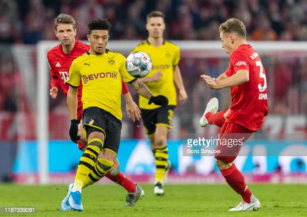 Jadon Sancho of Borussia Dortmund is challenged by Joshua Kimmich of FC Bayern Muenchen during the Bundesliga match between FC Bayern Muenchen and...