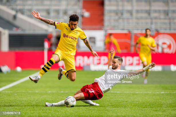 Jadon Sancho of Borussia Dortmund is challenged by Niko Giesselmann of Fortuna Duesseldorf during the Bundesliga match between Fortuna Duesseldorf...