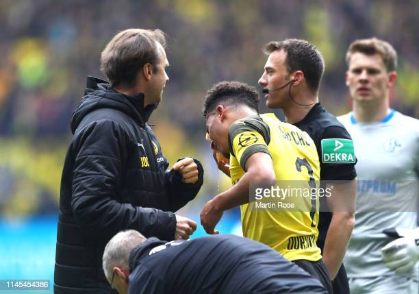 Jadon Sancho of Borussia Dortmund is given treatment as he is hit by an object as they celebrate their first goal during the Bundesliga match between...