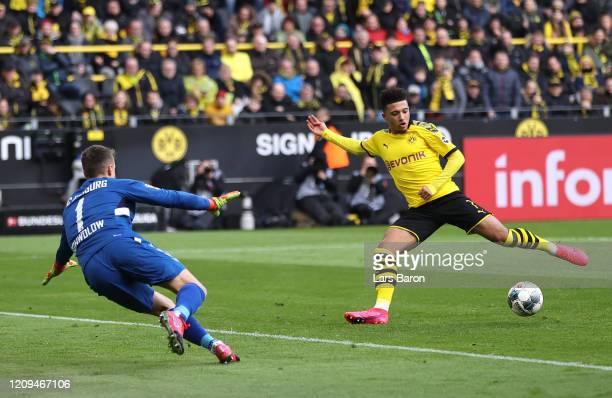 Jadon Sancho of Borussia Dortmund scores his sides first goal past Alexander Schwolow of Sport-Club Freiburg during the Bundesliga match between...