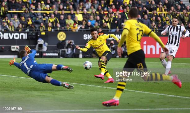 Jadon Sancho of Borussia Dortmund scores his sides first goal past Alexander Schwolow of SportClub Freiburg during the Bundesliga match between...