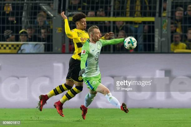 Jadon Sancho of Dortmund and Maximilian Arnold of Wolfsburg battle for the ball during the Bundesliga match between Borussia Dortmund and VfL...