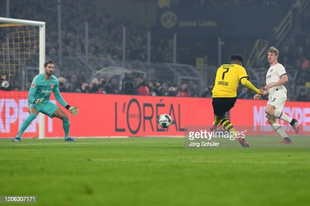 Jadon Sancho of Dortmund scores his team's second goal past goalkeeper Kevin Trapp of Frankfurt during the Bundesliga match between Borussia Dortmund...