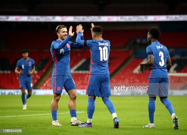 Jadon Sancho of England celebrates after scoring his team's second goal with Jack Grealish of England and Bukayo Saka of England during the...
