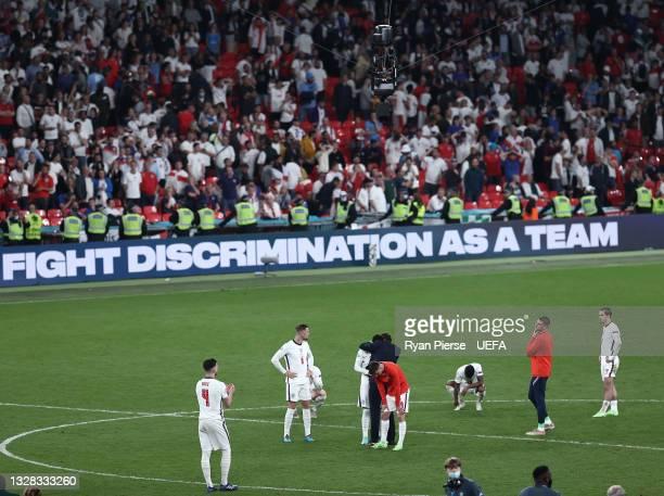Jadon Sancho of England is consoled by Gareth Southgate, Head Coach of England as , Jordan Henderson, Mason Mount, Raheem Sterling, Declan Rice and...