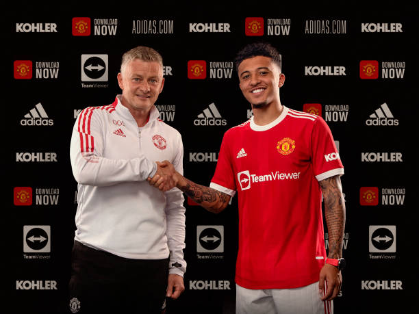 Jadon Sancho of Manchester United shakes hands with Manchester United Head Coach / Manager Ole Gunnar Solskjaer at Carrington Training Ground on July...