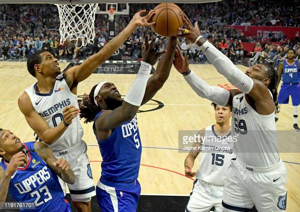 Jae Crowder and De'Anthony Melton of the Memphis Grizzlies defend Montrezl Harrell of the Los Angeles Clippers under the basket in the second half of...