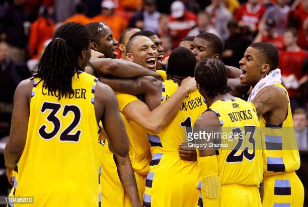 Jae Crowder, Joseph Fulce, Darius Johnson-Odom and Dwight Buycks of the Marquette Golden Eagles celebrate with teammates after defeating the Syracuse...