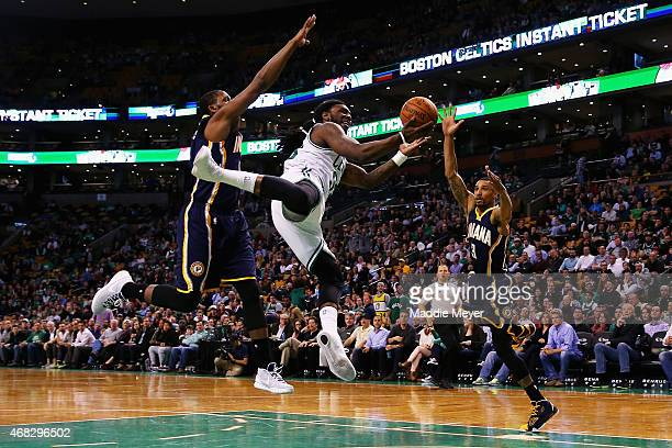 Jae Crowder of the Boston Celtics is fouled by George Hill of the Indiana Pacers with pressure from CJ Miles during the fourth quarter at TD Garden...