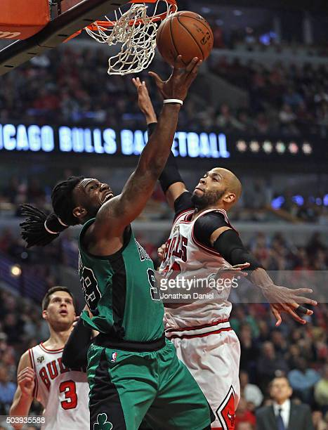 Jae Crowder of the Boston Celtics puts up a shot against Taj Gibson of the Chicago Bulls at the United Center on January 7 2016 in Chicago Illinois...