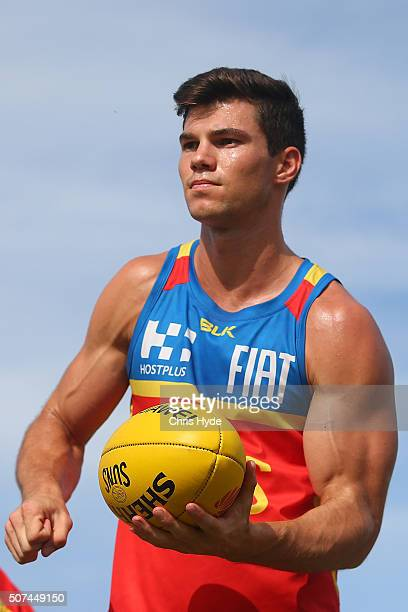 Jaeger O'Meara handballs during a Gold Coast Suns AFL beach training session at Palm Beach on January 30 2016 in Gold Coast Australia