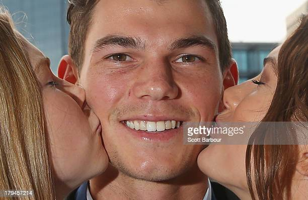 Jaeger O'Meara of the Gold Coast Suns is kissed by his sisters Jahni and Shaeli after winning the 2013 Ron Evans Medal NAB Rising Star Award as the...