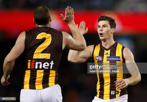 Jaeger O'Meara of the Hawks congratulates Jarryd Roughead of the Hawks on a goal during the 2018 AFL round 16 match between the Western Bulldogs and...
