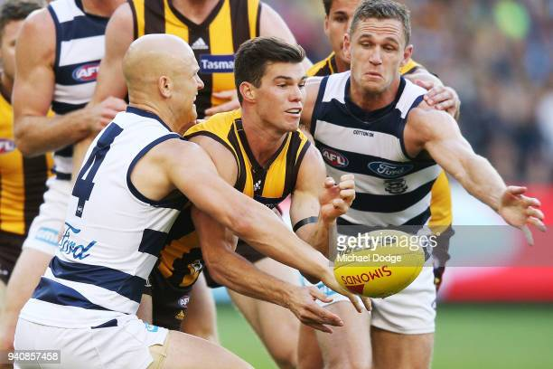 Jaeger O'Meara of the Hawks handballs between Gary Ablett of the Cats and Joel Selwood during the round two AFL match between the Geelong Cats and...
