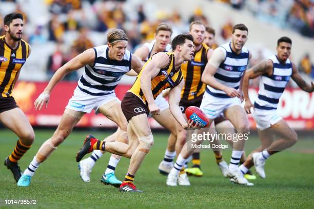 Jaeger O'Meara of the Hawks handballs from Rhys Stanley of the Cats during the round 21 AFL match between the Hawthorn Hawks and the Geelong Cats at...