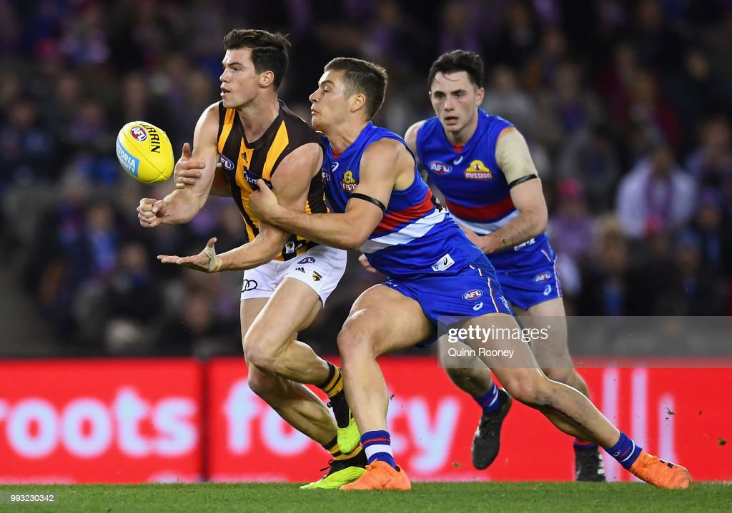 Jaeger O'Meara of the Hawks handballs whilst being tackled by Josh Dunkley of the Bulldogs during the round 16 AFL match between the Western Bulldogs and the Hawthorn Hawks at Etihad Stadium on July 7, 2018 in Melbourne, Australia.
