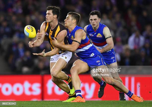 Jaeger O'Meara of the Hawks handballs whilst being tackled by Josh Dunkley of the Bulldogs during the round 16 AFL match between the Western Bulldogs...