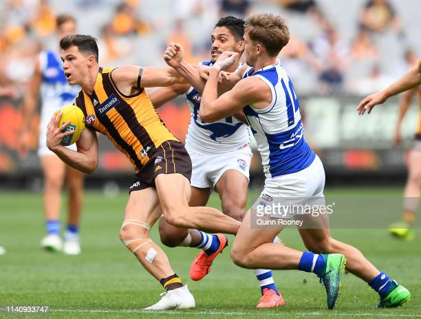 Jaeger O'Meara of the Hawks is tackled by Aaron Hall and Trent Dumont of the Kangaroos during the round three AFL match between the Hawthorn Hawks...