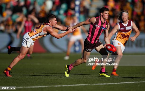Jaeger O'Meara of the Hawks is tackled by Dayne Zorko of the Lions during the 2018 AFL round 17 match between the Hawthorn Hawks and the Brisbane...