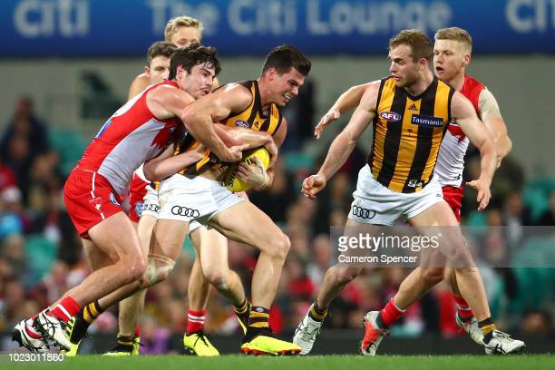 Jaeger O'Meara of the Hawks is tackled during the round 23 AFL match between the Sydney Swans and the Hawthorn Hawks at Sydney Cricket Ground on...