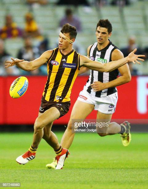 Jaeger O'Meara of the Hawks kicks the ball from Scott Pendlebury of the Magpies during the round one AFL match between the Hawthorn Hawks and the...