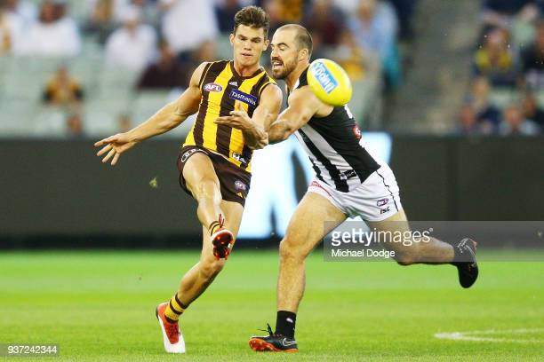 Jaeger O'Meara of the Hawks kicks the ball from Steele Sidebottom of the Magpies during the round one AFL match between the Hawthorn Hawks and the...